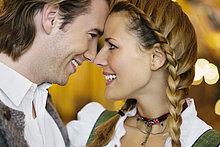 Junges Paar in Tracht, Stirn an Stirn, schauen sich in die Augen, Oktoberfest