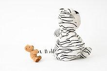 Kleiner Teddybär zieht großen ausgestopften Tigerschwanz