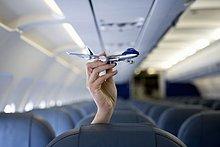 Eine Hand, die ein Spielzeugflugzeug über einem Flugzeugsitz hält.