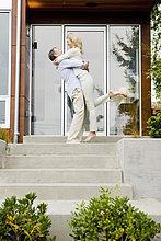 Mann umarmt und anheben Frau an front stoop