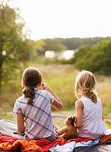 Zwei Mädchen sitzen auf einer Decke Schweden.