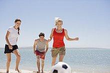 Freunde spielen Fußball am Strand