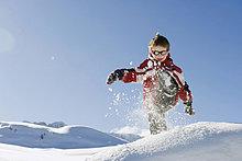 Italien, Südtirol, Seiseralm, Junge (4-5) beim Spielen im Schnee