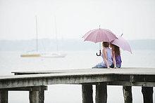 Zwei Frauen sitzen auf dem Steg, halten Regenschirm, Rückansicht