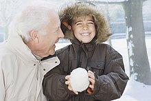 Großvater und Enkel mit Schneeball