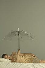Frau im Bett liegend mit geschlossenen Augen, Schirm hochhaltend