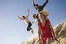 Zwei Paare an den Strand springen deaktiviert eine Sanddüne