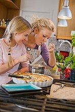 Mutter und Tochter mit einem frisch gebackenen Kuchen, Schweden.