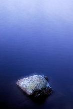 Ein Stein in einem kleinen See, Schweden.