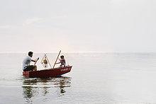 junge Mädchen und Vater im Ruderboot auf See