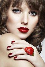 Junge Frau mit einem Ring aus einer Erdbeere,mund