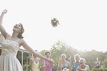 Braut wirft den Brautstrauß auf Hochzeitsfeier