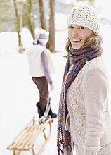 Mutter und Tochter ziehen Schlitten durch den Schnee