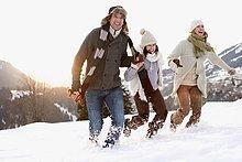Familie läuft durch Schnee