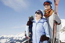 Paar mit Skiern steht auf winterlichem Berg
