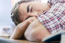 Männlicher Gymnasiast schläft in der Klasse