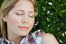 Junge Frau mit geschlossenen Augen auf Gras liegend