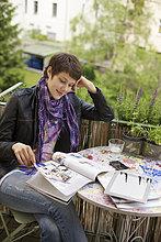 Junge Frau liest eine Zeitschrift auf dem Balkon