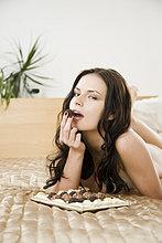 Frau essen Schokolade im Bett