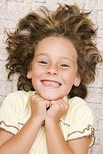 Lächelndes Mädchen, 6 Jahre, liegt auf dem Boden