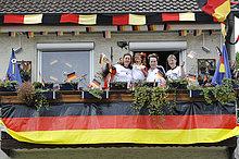 Fans der deutschen Nationalmannschaft in Nationaltrikots mit Deutschlandflaggen auf Balkon in geschmücktem Wohnhaus, Stuttgart, Baden-Württemberg, Deutschland, Europa