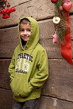 Kleiner Junge steht an der Holzwand einer Wanderhütte mit Weihnachtsdekoration