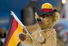 Muenchen, DEU, 01.07.2006 - Teddybaer mit Deutschlandfahne und Hut in schwarz-rot-gold.