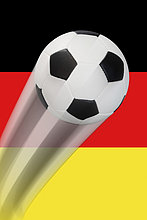 Ein Fußball fliegt durch die Luft vor einer Deutschlandflagge - Serie