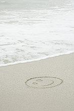 Smiley-Gesicht gezeichnet in Sand am Strand