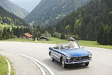 Seniorenpaar fährt mit Cabrio auf Landstraße, Italien, Telve