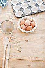 Eier und Backutensilien auf Holztisch
