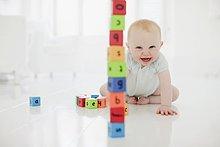Fröhliches Baby mit Turm aus Holzklötzen auf dem Fußboden