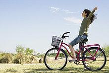 Junge Frau sitzt auf dem Fahrrad mit Waffen aus und geschlossenen Augen
