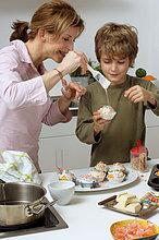 Mutter und Sohn backen Muffins