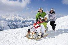 Lächelnder Familienschlitten im Schnee auf der Piste