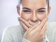 Junge Frau mit Händen über Mund