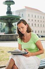 Junge Frau auf der Bank sitzend und lesend