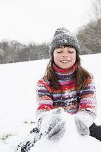 Mädchen baut Schneemann