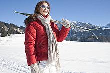 Frau mit Skiern in Winterlandschaft, Tannheimer Tal, Tirol, Österreich