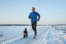 Mann joggt mit Hund im Schnee, Tannheimer Tal, Tirol, Österreich