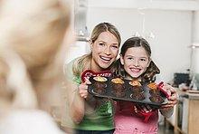 Deutschland, , Mutter und Tochter halten Törtchen im Backblech, lächelnd