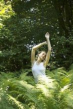 Porträt einer jungen Frau, die sich zwischen Farnblättern im Freien ausbreitet.