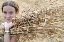 Mädchen hält Bündel von Weizen