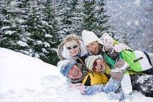 Porträt der lächelnden Familie im Schnee liegend
