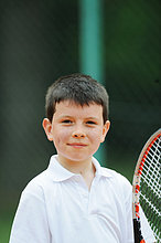 Portrait Of Young Boy Holding Tennis Racket
