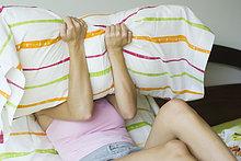Junge Frau im Bett, covering Face mit Kissen