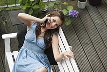Junge Frau mit Handy auf Bank, lächelnd, Portrait