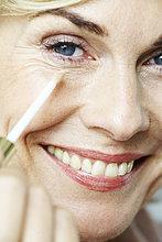 Nahaufnahme der Reife Frau Anwendung Concealer unter Auge