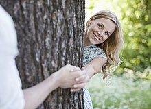 Paar hält Händchen um einen Baum herum