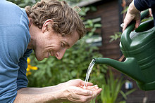 Man holding water poured from watering can